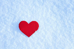 Greeting card with lonely heart on the dazzling blue snow stock photography