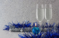 Greeting card made of christmas and yew year decoration balls, tinsel, candel  and two glasses of champagne with reflection Royalty Free Stock Images