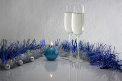 Greeting card made of christmas and yew year decoration balls, tinsel, candel  and two glasses of champagne with reflection Stock Image