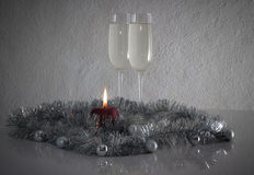 Greeting card made of christmas and yew year decoration balls, tinsel, candel  and two glasses of champagne with reflection Stock Photos