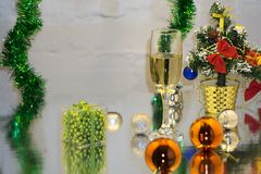 Greeting card made of christmas and yew year decoration balls, tinsel, candle and two glasses of champagne with reflection, copy s stock photography