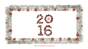 Greeting card made of silver tinsel frame with red christmas balls, 2016 made of corns and chinese hieroglyph for monkey. New year greeting card made of silver royalty free stock photography