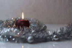 Greeting card made of silver tinsel with silver christmas balls and red burning candle Stock Photos