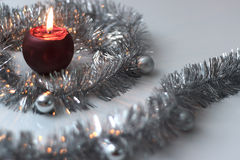 Greeting card made of silver tinsel with silver christmas balls and red burning candle Royalty Free Stock Images