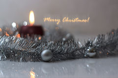 Greeting card made of silver tinsel with silver christmas balls and red burning candle Stock Photography