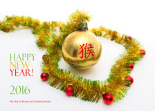 Greeting card made of yellow and green tinsel frame with red and golden christmas balls and chinese hieroglyph for monkey Stock Photo
