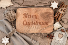 Greeting card Merry Christmas on wood. Greeting card Merry Christmas burnt on wooden board with winter decorations around Royalty Free Stock Photography