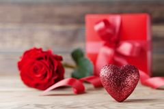 Greeting card for Mother or Valentines day. Heart, gift and rose flower on rustic wooden table. Greeting card for Mother or Valentines day. Heart, gift and rose Royalty Free Stock Photo