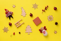 Greeting card for New year party. Christmas gifts, decorative elements and ornaments on yellow background. Top view, copy space. Winter holiday concept royalty free stock photography