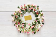 Greeting card in pink natural roses frame on white rustic wood stock photography