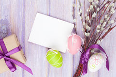 Greeting card, willow and easter eggs. Over wooden table background with copy space Royalty Free Stock Image