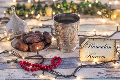 Greeting card Ramadan Kareem with dates, rosary, and metal water cup with Allah text in arabic. With lights background stock photos