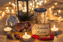Greeting card Ramadan Kareem with dates, rosary, and metal water cup with Allah text in arabic. On wooden table royalty free stock photo
