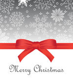 Greeting card with red bow on snowflakes background and copy space Royalty Free Stock Images
