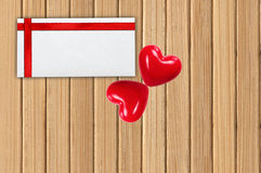 Greeting card with red ribbon and two red hearts on wooden plank Stock Photos