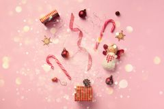 Greeting card with snow, lights bokeh for New year party. Christmas gifts, decorative elements and ornaments on pink background. Top view. Winter holiday stock photo