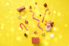 Greeting card with snow, lights bokeh for New year party. Christmas gifts, decorative elements and ornaments on yellow background. Top view. Winter holiday stock photography