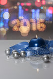 Greeting card template made of blue candle with blue ribbon, silver christmas balls, silver string of beads and colorful bokeh lig Stock Images