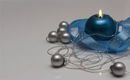 Greeting card template made of blue candle with blue ribbon, silver christmas balls and silver string of beads Royalty Free Stock Images