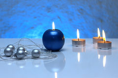 Greeting card template made of blue and tea candles, silver christmas balls, silver string of beads and blue ribbon in front Stock Photography