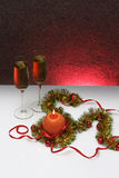 Greeting card template made of golden and green tinsel with red christmas balls, red ribbon, orange candle and two glasses of cham Royalty Free Stock Photography