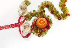 Greeting card template made of golden and green tinsel with red christmas balls, red ribbon, orange candle and two glasses of cham Royalty Free Stock Photo