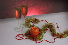 Greeting card template made of golden and green tinsel with red christmas balls, red ribbon, orange candle and two glasses of cham Stock Images