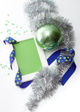 Greeting card template made of white frame and green card with blue ribbon, green ball, silver tinsel and confetti Royalty Free Stock Image