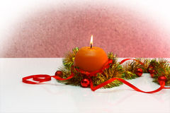 Greeting card template made of yellow and green tinsel with red and golden christmas balls, red ribbonand orange candle Stock Photography