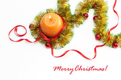 Greeting card template made of yellow and green tinsel with red and golden christmas balls, red ribbonand orange candle Royalty Free Stock Photo