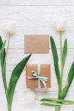 Greeting card  template with stylish present box and tulips on w. Hite wooden rustic background. flat lay with flowers and empty paper with space for text Royalty Free Stock Photos
