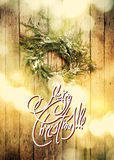Greeting Card with Text Merry Christmas on Background from Green Natural Wreath. Light Boke. Toned Royalty Free Stock Photos