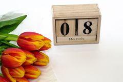 Greeting card for 8th March. International Women`s day background with bouquet of red tulips and wooden calendar of 8 march. Copy stock photos