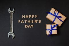 Greeting card to celebrate Father`s day. Two craft gifts with blue ribbons with tool on paper black background royalty free stock images