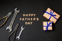 Greeting card to celebrate Father`s day. Two craft gifts with blue ribbons with tools on paper black background. Top view stock photo