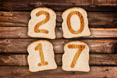 2017 greeting card toasted slices of bread on wood planks background Stock Image