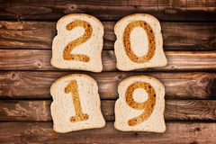 2019 greeting card toasted slices of bread on wooden planks. Background royalty free stock photos