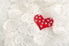 Greeting card for valentine's day. A red heart on white lace background Stock Images