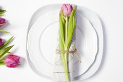 Greeting card for Valentine`s day. Decoration of the wedding table. On a plate a napkin with a tulip, beautifully tied. Stock Images