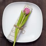 Greeting card for Valentine`s day. Decoration of the wedding table. On a white plate a napkin with a tulip, beautifully tied. Woo Stock Photography