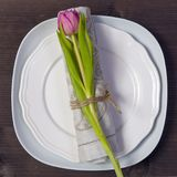 Greeting card for Valentine`s day. Decoration of the wedding table. On a white plate a napkin with a tulip, beautifully tied. Woo Royalty Free Stock Photos