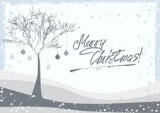 Greeting card with winter tree. Grunge retro style greeting card with winter tree on meadow decorated with Christmas balls and hand written lettering on grey Royalty Free Stock Image