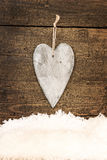 Greeting card with a wooden heart and snowflakes Royalty Free Stock Photography