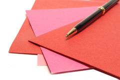Greeting cards. Pen resting on a pile of red and pink greeting cards Royalty Free Stock Image