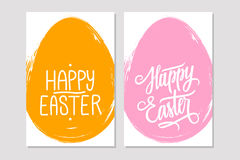 Greeting cards with handwritten holiday wishes of a Happy Easter and brush stroke egg shape background. Royalty Free Stock Photo