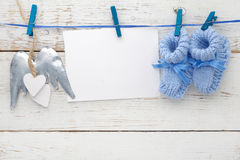 Greeting children form with blue booties and wings. Flat lay Stock Photo