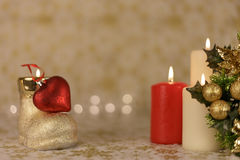 Greeting Christmas card with burning candles and ornaments. Greeting Christmas card with burning candles, golden decoration and yellow lights Stock Photo