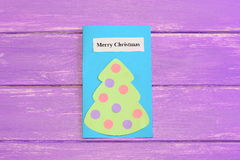 Greeting Christmas card isolated on lilac wooden background. Homemade paper card with Christmas tree and wishes Merry Christmas Royalty Free Stock Image