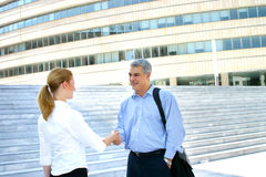 Greeting colleagues.. Two business colleagues meet and exchange greetings with shaking hands.  Outdoor shot showing a business compound in background Royalty Free Stock Photography