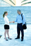 Greeting colleagues.. Two business colleagues meet and exchange greetings with shaking hands.  Outdoor shot showing a business compound in background. Portrait Royalty Free Stock Images